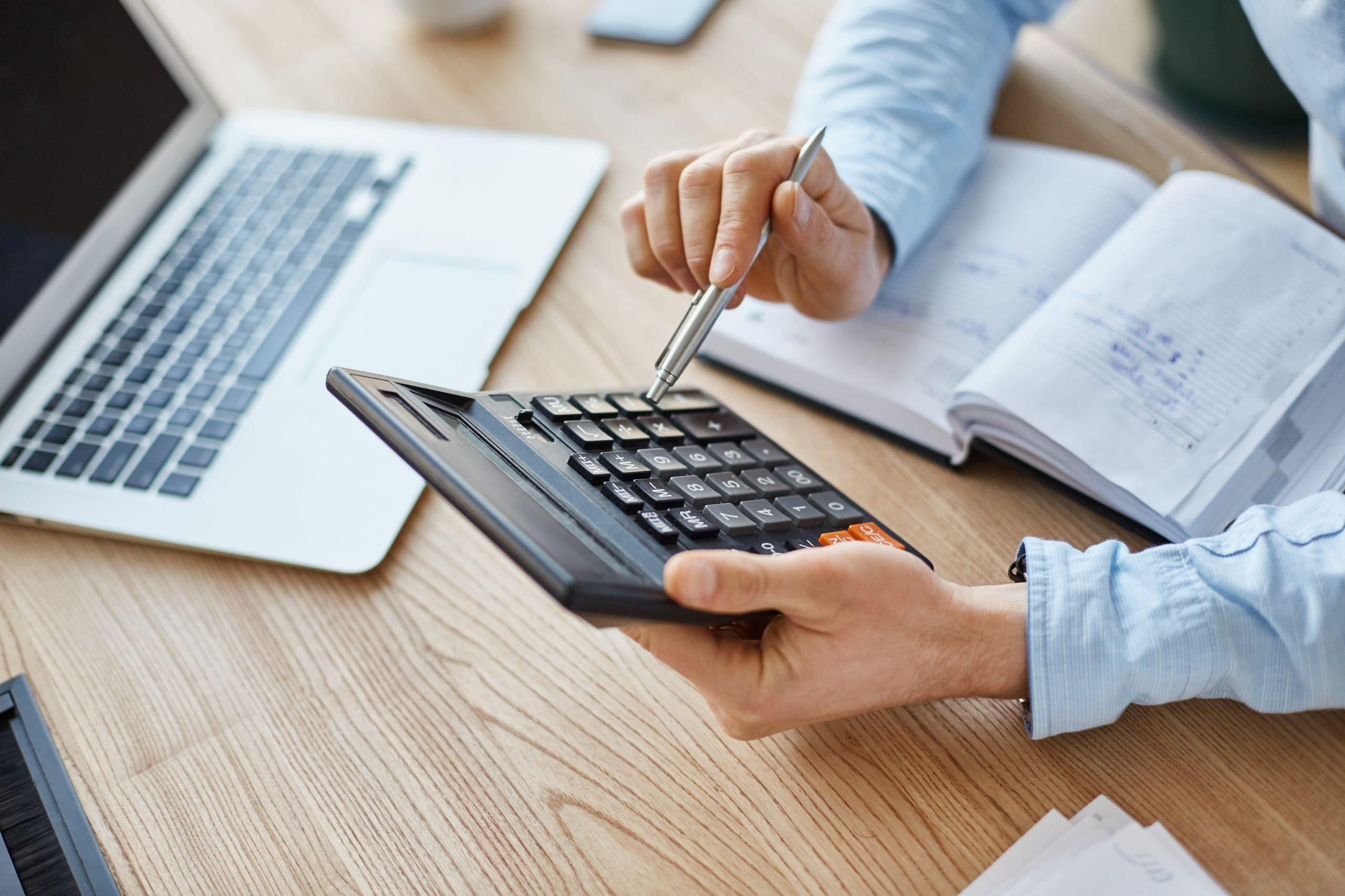 Cropped view of professional serious finance manager, holding calculator in hands, checking company month's profits, looking through details on laptop, writing down information for meeting with director.